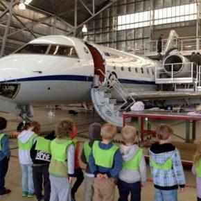 Children in aircraft hanger with aeroplane