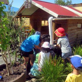 Children in garden installing water tank