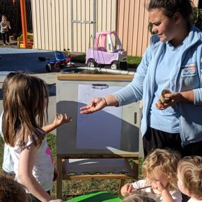 Educator with pre-school students outdoors