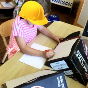 Child sketching whilst wearing a hardhat