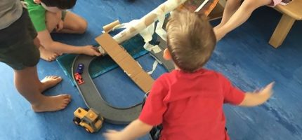 Children making a car tunnel with a long paper roll