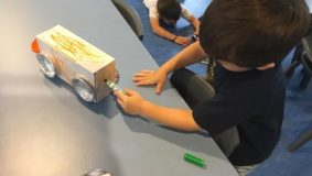 Child making a toy car out of a box with foil wheels