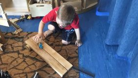 Child pushing a toy car along a wooden board