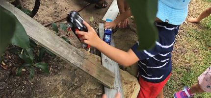 Children pushing toy cars around a wooden plank track