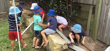 Children pushing toy cars along wooden planks