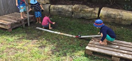 Children pushing a toy car down a wooden plank