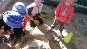 Children watching a volcano in a sandpit erupting