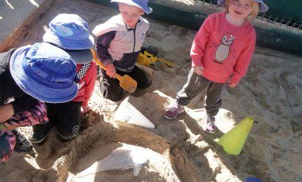 Children watching a volcano in a sandpit erupting