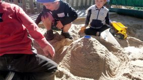 Children making a sandpit volcano