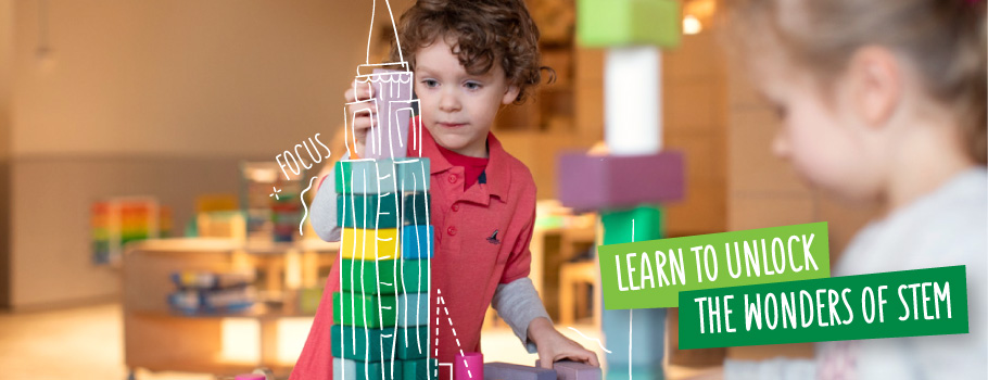 Learn to unlock the wonders of STEM - Boy building block tower