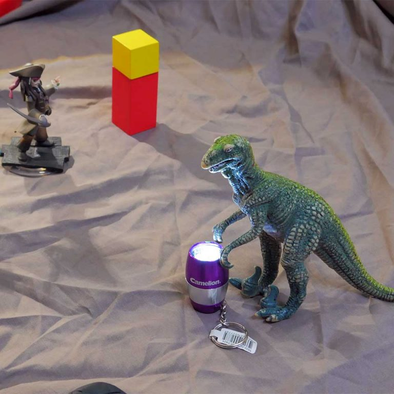 Torch shining on toy dinosaur