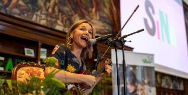 Justine Clarke singing and playing ukulele