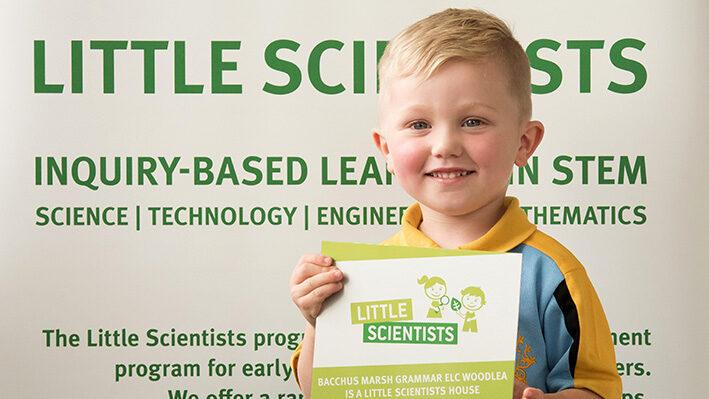 Boy holding a Little Scientists House plaque