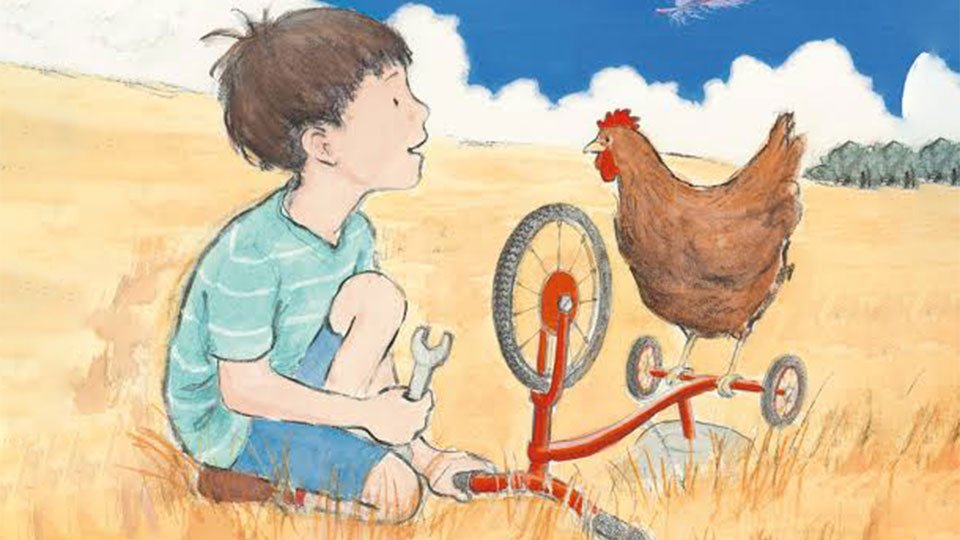 Boy in field with bike and chicken