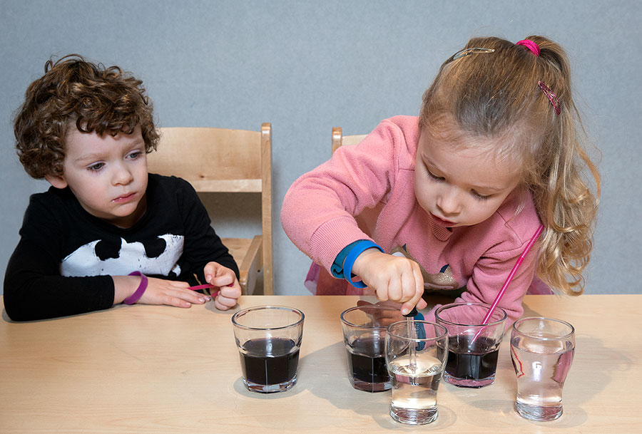 Girl and boy examining coloured glasses of water