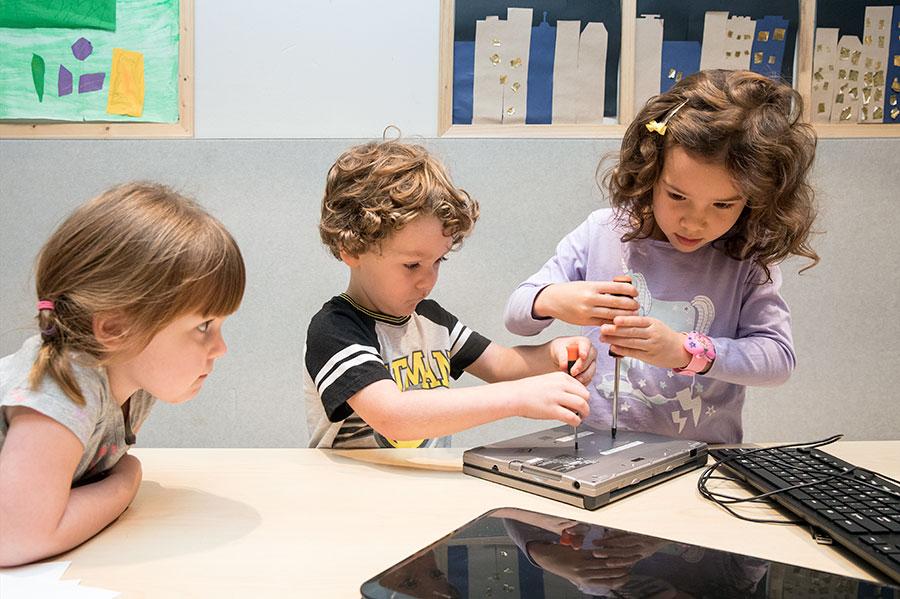 Preschoolers using screwdriver to open a computer
