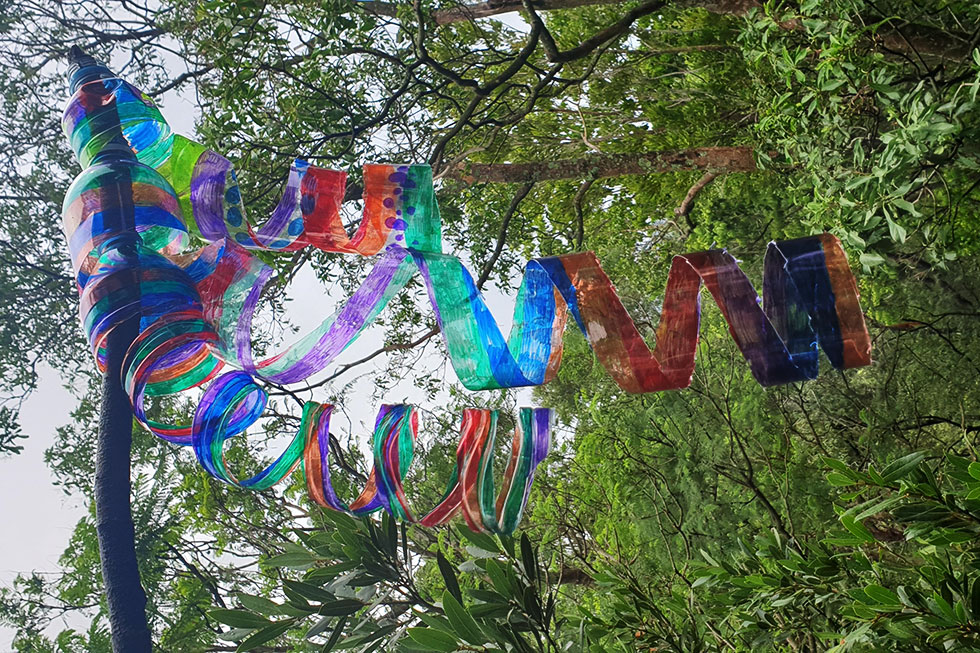 Colourful spirals made from plastic bottles blowing in breeze near trees