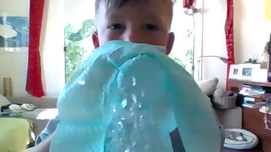 Child blowing bubble mix through chux cloth to make a snake