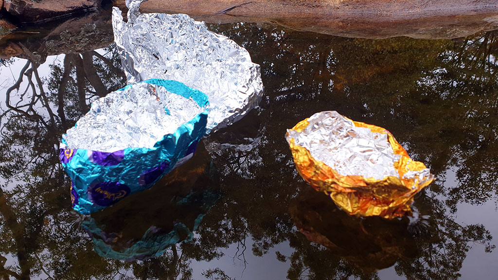Coloured tinfoil shaped into boats floating on pond