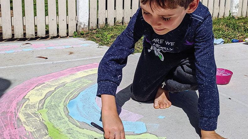 Boy painting rainbow on path
