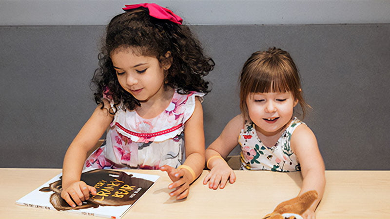 Kids playing with book and stuffed animal