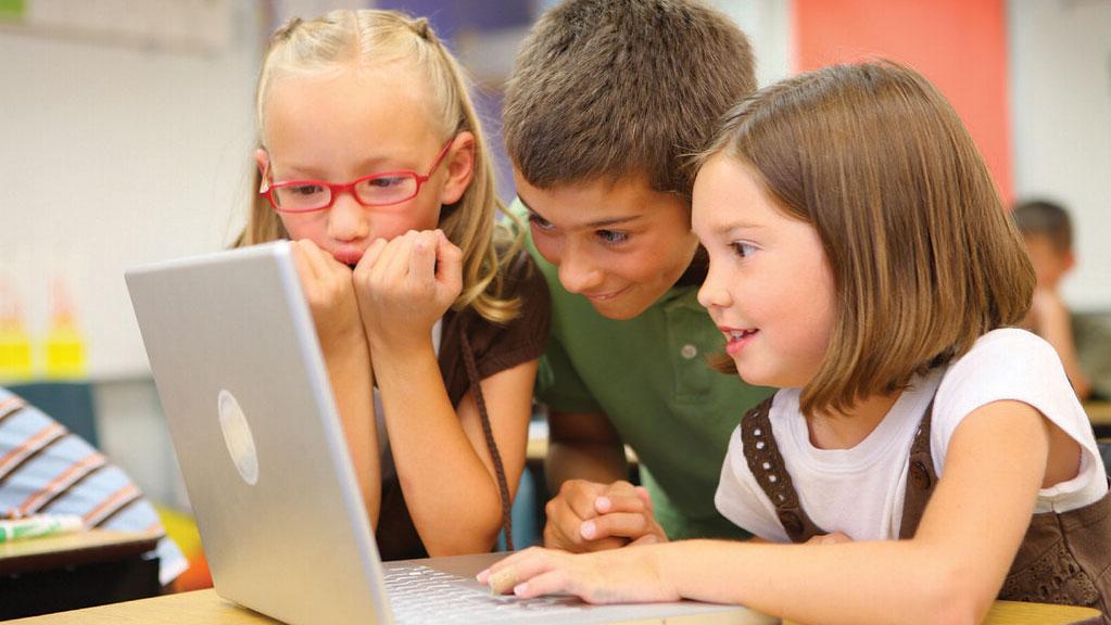 3 kids looking at laptop screen