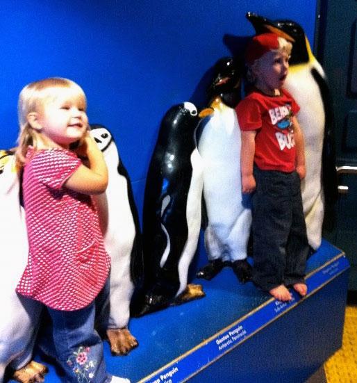 Children standing next to penguin statues