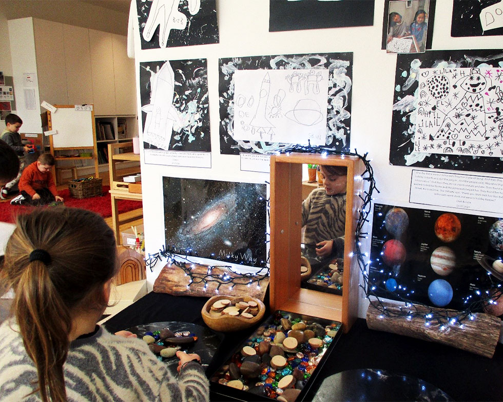 Child at table with space themed objects
