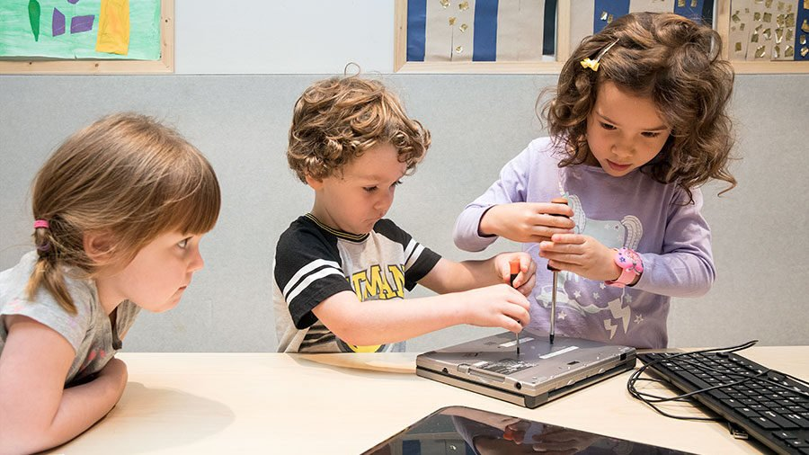 children unscrewing a device to see inside