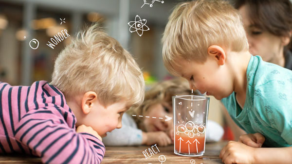 Boys looking into glass with coloured water