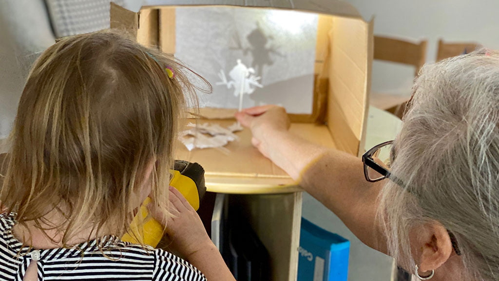Child with educator shining a light into a box to make shapes