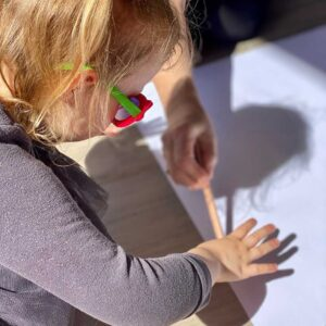 child tracing her hand shadow