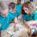Kids putting flowers into honey