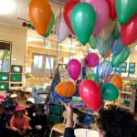Children with lots of coloured balloons