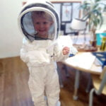 child in bee keeping suit