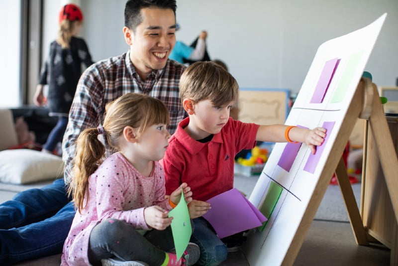 Children pasting squares onto board