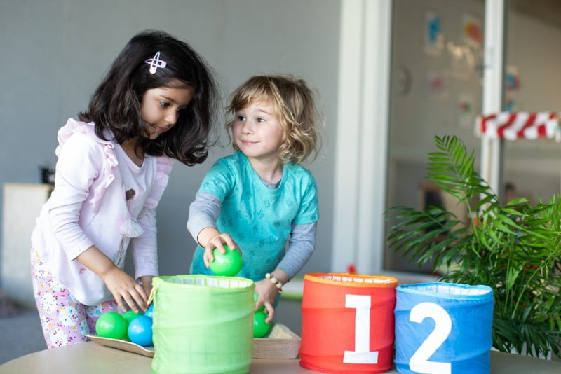 Children placing balls into numbered baskets