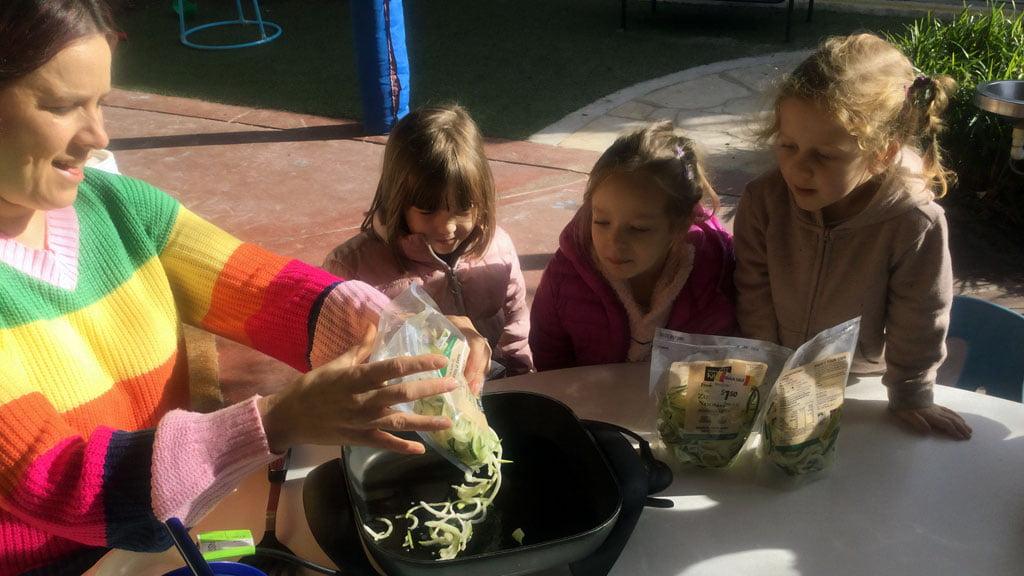 Children and teacher cooking zucchini