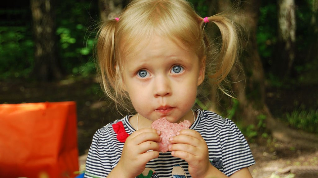 Child looking sad whilst eating meat